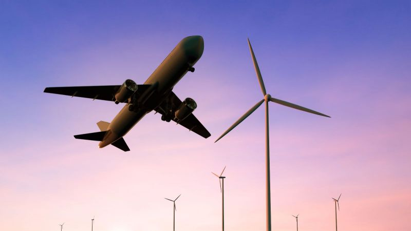Das Bild zeigt ein aufsteigendes Flugzeug vor Windmühlen.