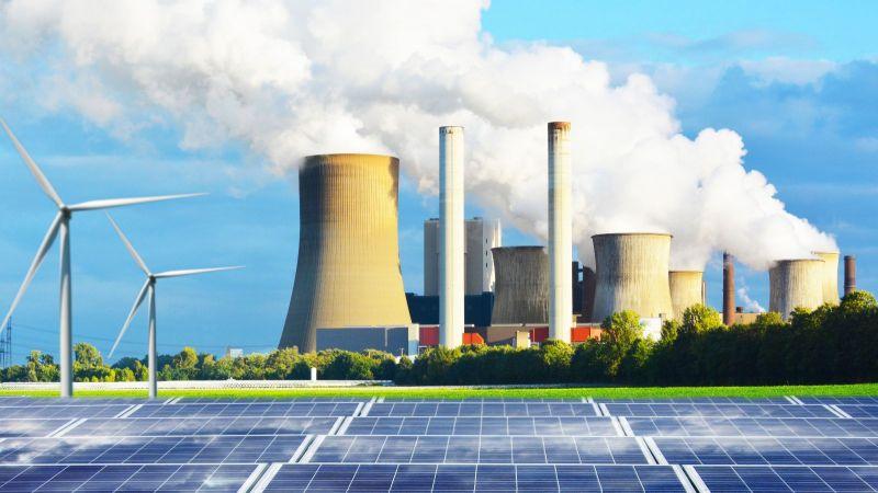 Das Bild zeigt Solarpaneele und Windräder neben einem Kohlekraftwerk.