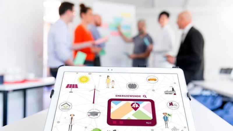 Das Foto zeigt Menschen, die diskutieren und ein iPad im Vordergrund des Bildes.