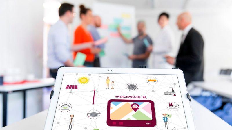 Das Bild zeigt Menschen, die hinter einem Tablet diskutieren.