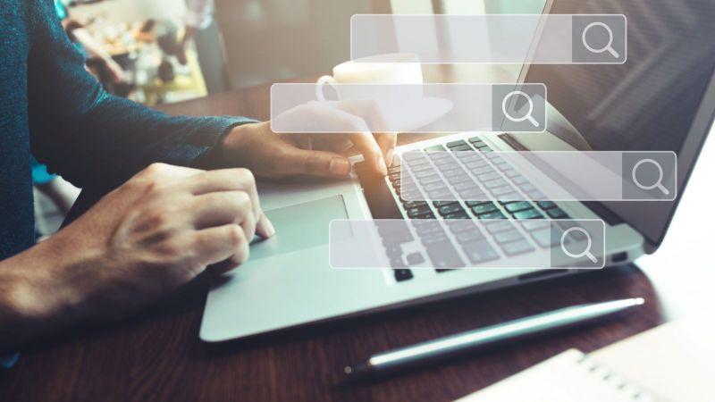 Das Bild ist eine Fotomontage. Es ist eine Person an einem Laptop zu sehen und Felder einer Suchfunktion.