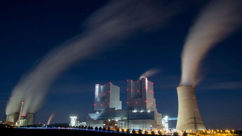 Das Bild zeigt ein Kohlekraftwerk bei nach, aus dessen Schornsteinen Rauch in dicken Schwaden zieht.
