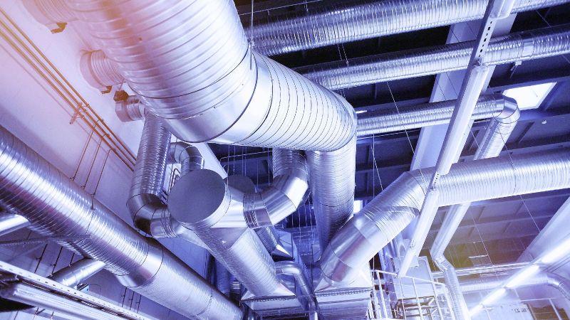 Das Foto zeigt Rohre industrieller Kälte und Wärmeversorgung an einer Decke.