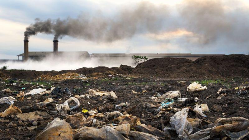 Das Bild zeigt eine verschmutzte und vermüllte Landschaft vor einer Fabrik, die schwarzen Rauch ausstößt.