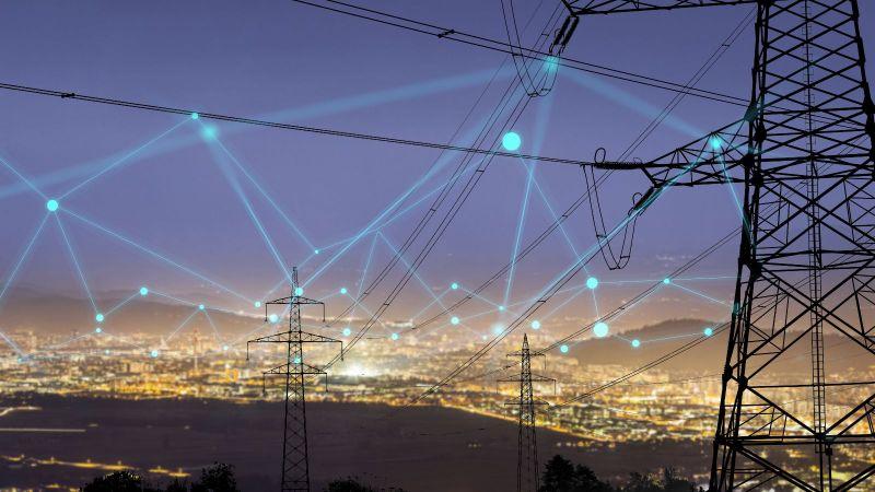 Das Bild ist eine Fotomontage. Es sind Strommasten und Stromleitungen zu sehen, die durch blaue Linien netzartig miteinander verbunden sind.