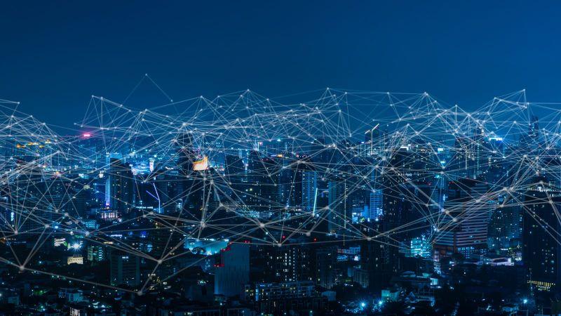 Das Bild ist eine Fotomontage. Es zeigt eine Stadt bei Nacht, über die sich ein digitales Netz spannt.