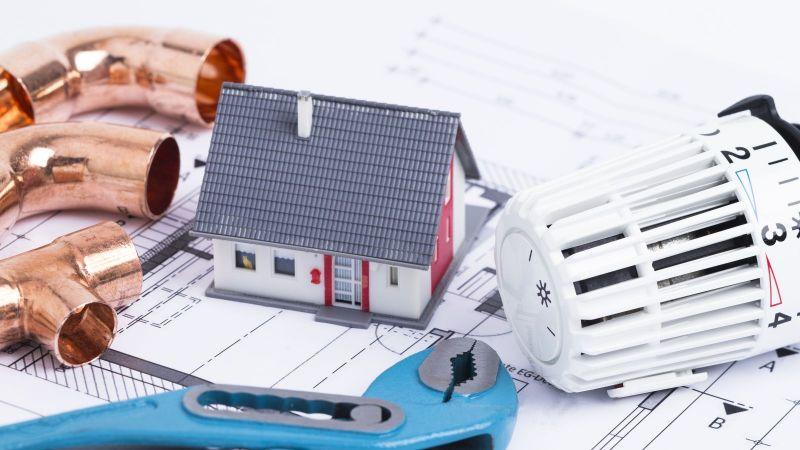 Das Bild zeigt einen Heizkopf, eine Rohrzange, ein Heizrohr und eine Mini-Modell eines Einfamilienhauses, die auf einem Bauplan platztiert wurden.