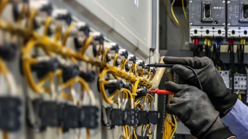 Das Bild zeigt zwei Hände vor einem Panel, in dem diverse Kabel stecken. Die Hände stecken gerade ein Kabel um.