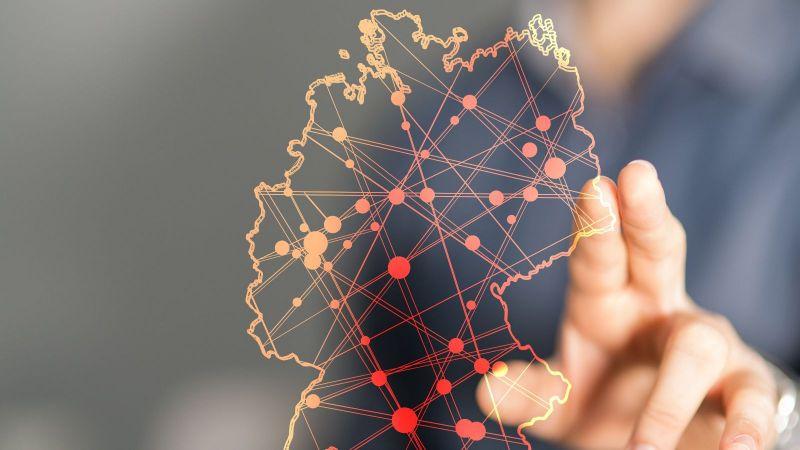 Das Bild ist eine Montage. Es ist eine transparente Deutschlandkarte zu sehen, auf der mehrere Orte miteinander verbunden sind. Dahinter steht ein Mann, der einen Punkt auf der Karte zeigt.