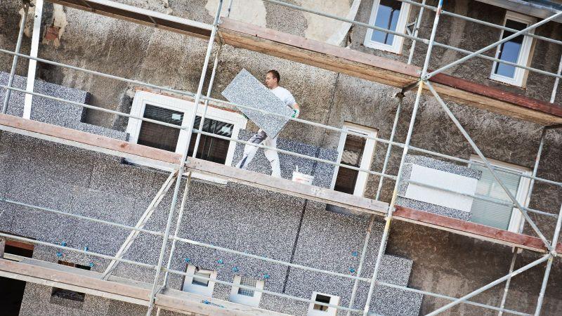 Das Bild zeigt einen Bauarbeiter auf einem Gerüst vor einem halb gedämmten Gebäude. Der Bauarbeiter trägt eine Dämmplatte in der Hand.