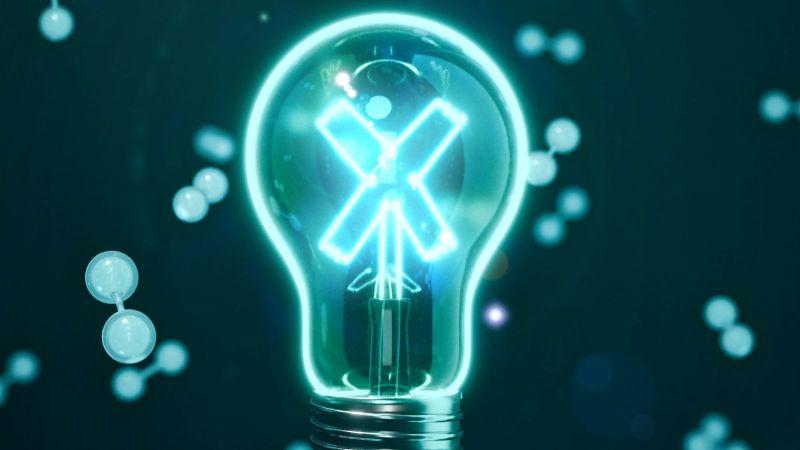 Das Bild zeigt eine Glühbirne, deren Glühfäden ein X bilden. Im Hintergrund sind diverse Moleküle zu erkennen.