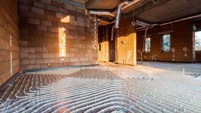 Das Bild zeigt den Fußboden eines Neubaus, auf dem gerade Warmwasser-Schläuche für die Beheizung verlegt werden.