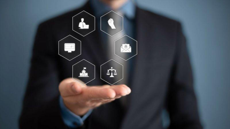 Das Bild zeigt eine Fotomontage: Ein Mann in Anzug hält zeigt mehrere Symbole aus dem Bereich Justiz.