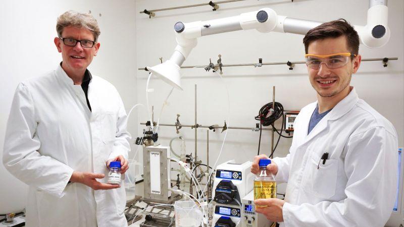 Das Bild zeigt zwei Wissenschaftler vor einem Elektrolyseur, mit dessen Hilfe sie klimafreundliche Carbonsäuren hergestellt haben.