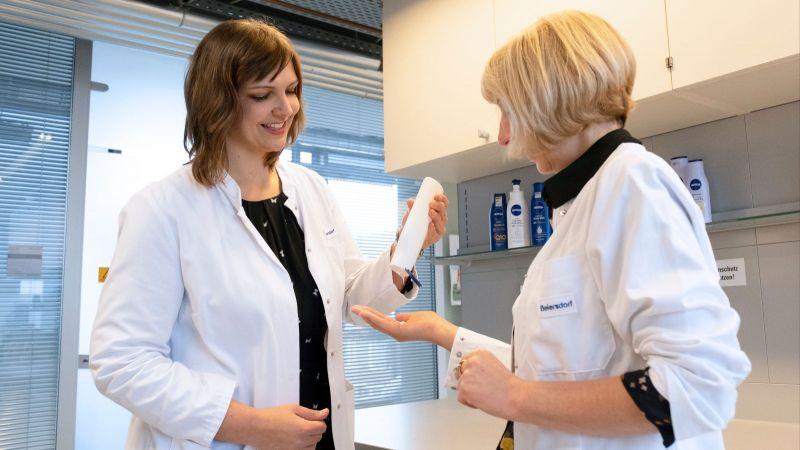 Das Bild zeigt zwei Forscher, die ein Hautpflegeprodukt untersuchen.