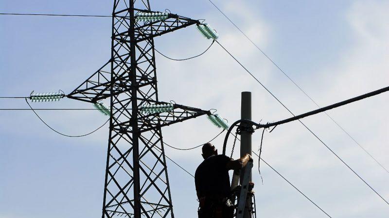Das Bild zeigt eine Person bei Arbeiten an einer Stromleitung.