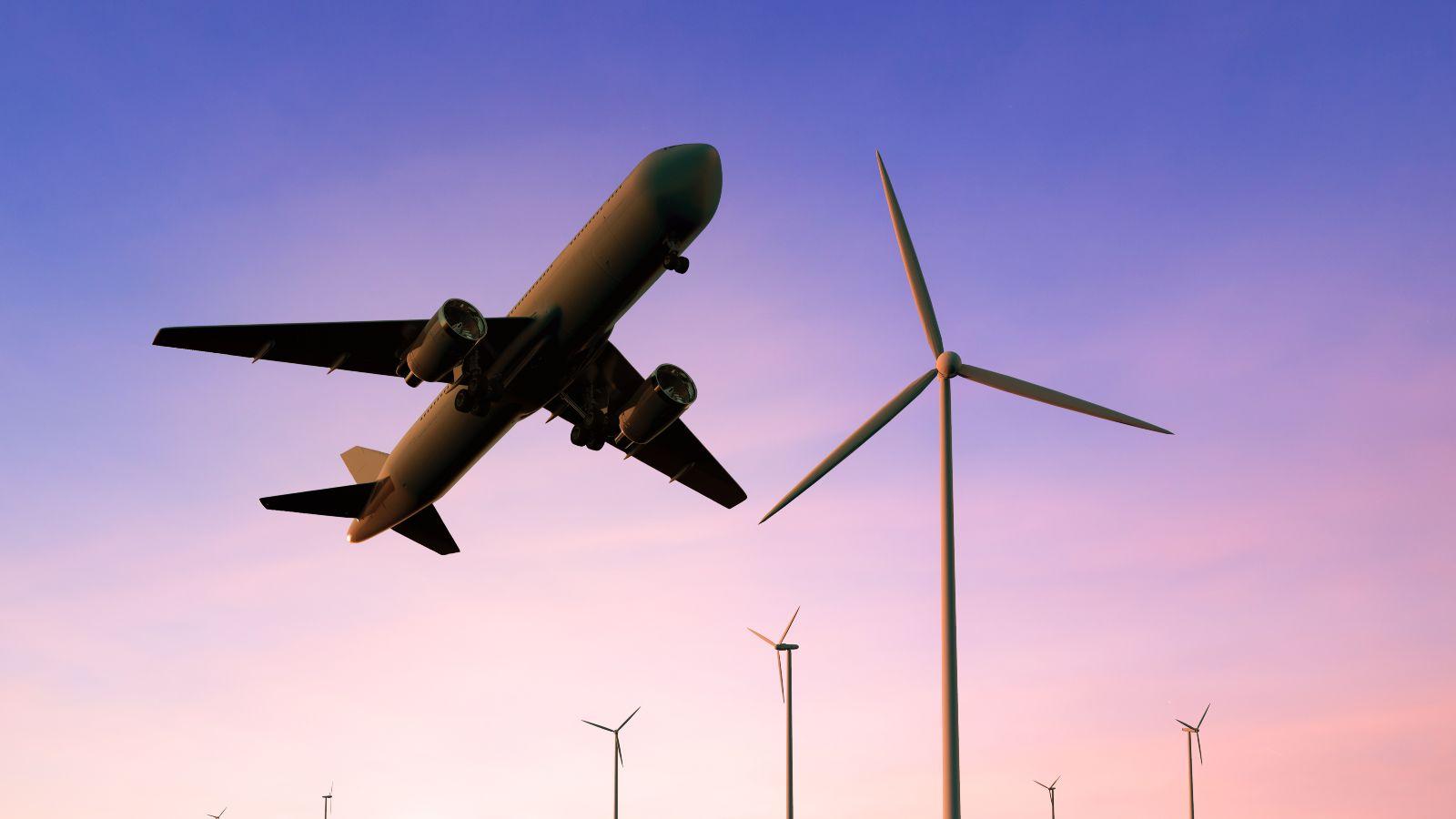 Das Bild zeigt ein Flugzeug über einigen Windrädern.