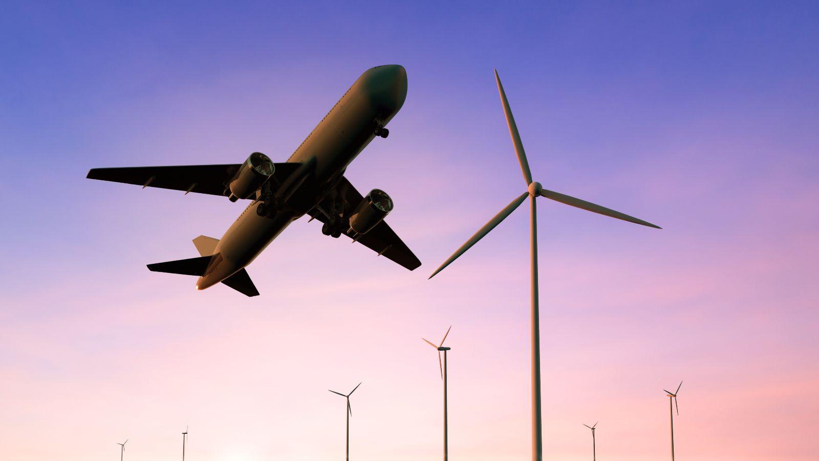 Das Foto zeigt ein Flugzeug, das über einige Windräder hinweg fliegt.