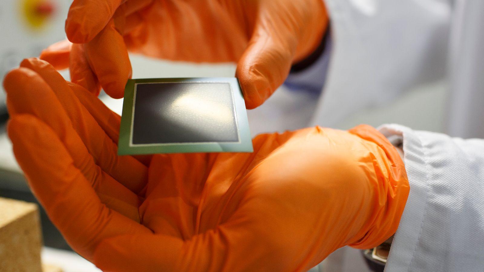 Das Bild eine Hand, die eine Iridium-beschichtete Katalysatoren-Platte zeigt.