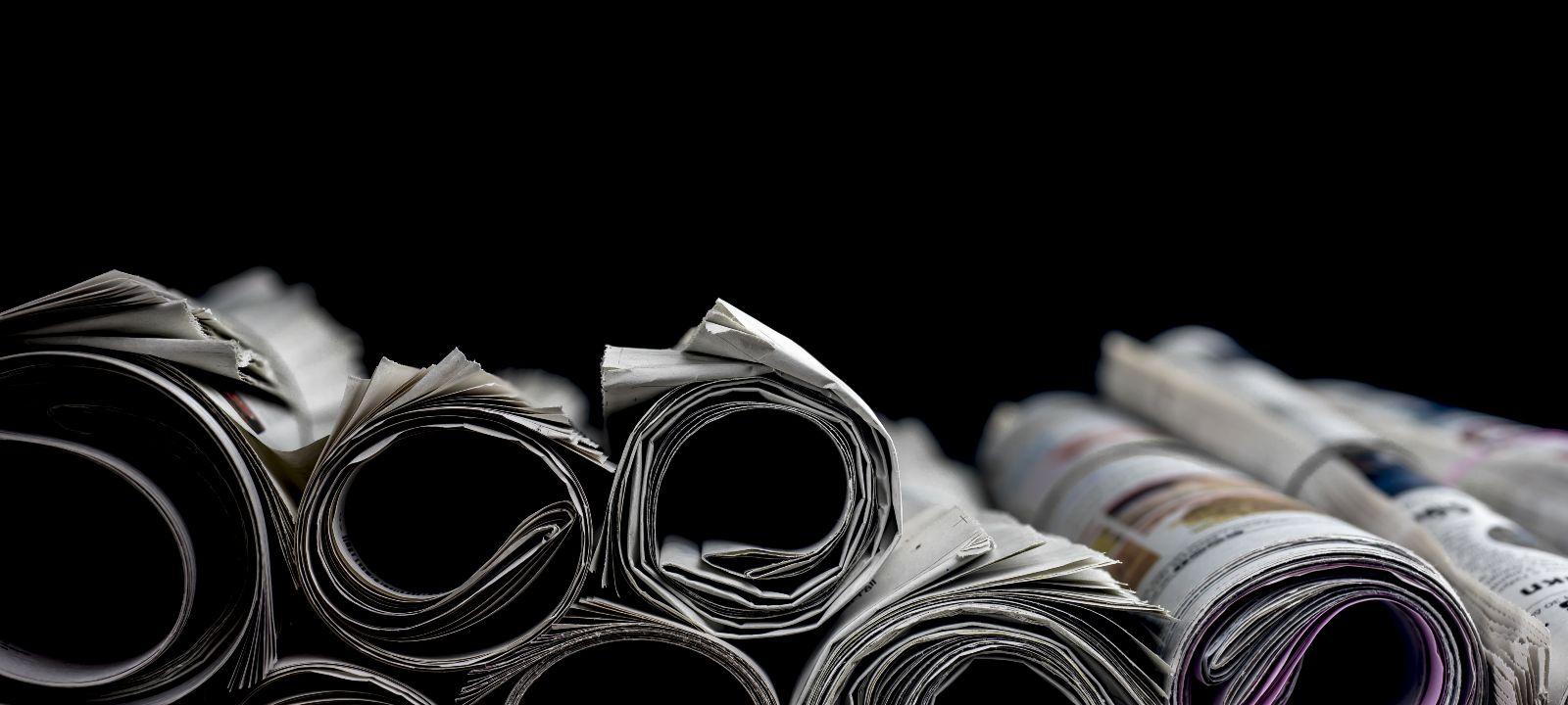 Das Bild zeigt zusammengerollte Zeitungen vor schwarzem Hintergrund.